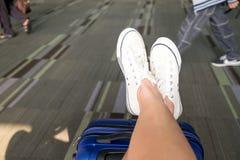 Fermez-vous vers le haut de l'espadrille blanche d'usage croisé de jambe étendue sur la valise à l'aéroport Photo stock