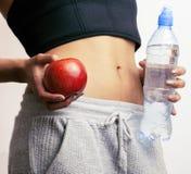 Fermez-vous vers le haut de l'estomac de femme avec des mains tenant l'eau Photographie stock libre de droits