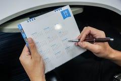 Fermez-vous vers le haut de l'homme d'affaires avec le plan de stylo rencontrant le 2017 le calendrier Images stock