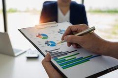 Fermez-vous vers le haut de l'homme d'affaires et de l'associé montrant le revenu pour calaulating image stock
