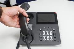 Fermez-vous vers le haut de l'homme d'affaires outre de l'exigence de téléphone d'IP de crochet photo stock