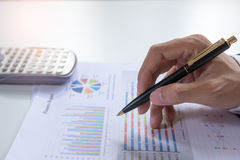 Fermez-vous vers le haut de l'homme d'affaires que le contrôle analyse sérieusement des collègues d'un investisseur de rapport de Photographie stock