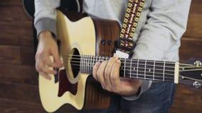 Fermez-vous vers le haut de l'homme jouant le mouvement lent de guitare acoustique banque de vidéos
