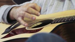 Fermez-vous vers le haut de l'homme jouant le mouvement lent de guitare acoustique clips vidéos