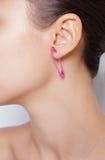 Fermez-vous vers le haut de l'image de l'oreille femelle avec la boucle d'oreille images stock