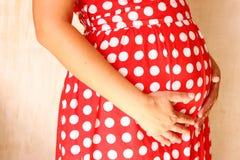 Fermez-vous vers le haut de l'image de la femme enceinte méconnaissable touchant son ventre avec ses mains Photos stock