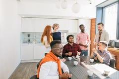 Fermez-vous vers le haut de l'image des jeunes prenant le thé au travail Images stock