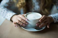 Fermez-vous vers le haut de l'image des mains de femme secouant le cappuccino au café Photos libres de droits