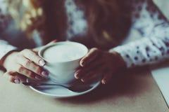 Fermez-vous vers le haut de l'image des mains de femme secouant le cappuccino au café Images libres de droits