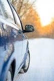 Fermez-vous vers le haut de l'image du rétroviseur latéral sur une voiture dans le paysage d'hiver avec la soirée Sun photos stock