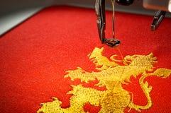 Fermez-vous vers le haut de l'image de la machine de broderie et brodez le lion d'or sur le tissu rouge Photos libres de droits