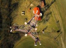 Fermez-vous vers le haut de l'image de la tour BTS de station d'émetteur-récepteur basse sur le pré vert et la forêt d'en haut pr Images libres de droits