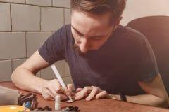 Fermez-vous vers le haut de l'insigne de peinture de métier de main de l'homme du bois par le marqueur permanent sur le lieu de t photo stock