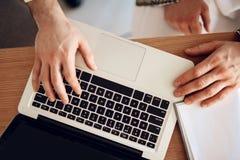 Fermez-vous vers le haut de l'ordinateur portable sur la table avec trois mains photo stock