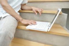 Fermez-vous vers le haut de l'ordinateur portatif sur des escaliers Photo stock