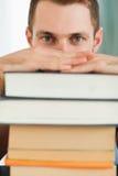 Fermez-vous vers le haut de l'étudiant se cachant derrière une pile des livres Photos libres de droits