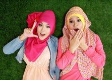 Fermez-vous vers le haut de la belle femme deux musulmane heureuse se trouvant sur l'herbe Image libre de droits