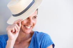 Fermez-vous vers le haut de la belle femme mûre souriant avec le chapeau contre le mur blanc Image libre de droits