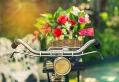 Fermez-vous vers le haut de la bicyclette de vintage avec des fleurs de bouquet dans le panier Photographie stock