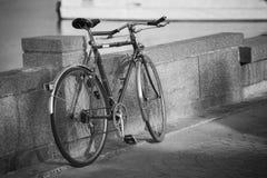 Fermez-vous vers le haut de la bicyclette de vintage s'étendant près d'un mur, style noir et blanc de photo, bords foncés, foyer  Photos libres de droits