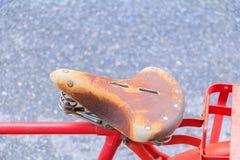 Fermez-vous vers le haut de la bicyclette en cuir de selle le vintage classique que rouge dans ancien beau avec l'espace de copie photographie stock libre de droits