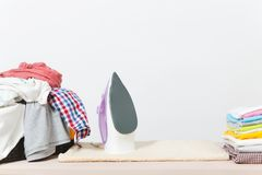 Fermez-vous vers le haut de la blanchisserie lavée par vêtements colorés de fer de vapeur sur le fond blanc ménage Copiez la publ images libres de droits