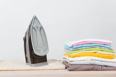 Fermez-vous vers le haut de la blanchisserie lavée par vêtements colorés de fer de vapeur sur le fond blanc ménage Copiez la publ photos stock
