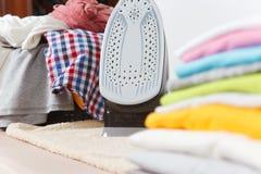 Fermez-vous vers le haut de la blanchisserie lavée par vêtements colorés de fer de vapeur sur le fond blanc ménage Copiez la publ photographie stock