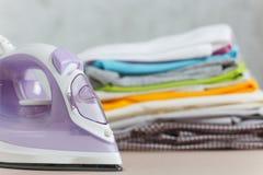 Fermez-vous vers le haut de la blanchisserie lavée par vêtements colorés de fer de vapeur sur le fond blanc ménage Copiez la publ image stock