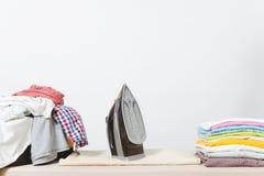 Fermez-vous vers le haut de la blanchisserie lavée par vêtements colorés de fer de vapeur sur le fond blanc ménage Copiez la publ image libre de droits