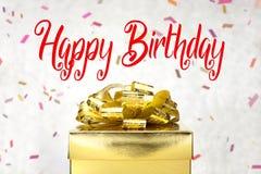 Fermez-vous vers le haut de la boîte actuelle d'or avec le mot et le confett de joyeux anniversaire Photo libre de droits