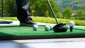 Fermez-vous vers le haut de la boule sur le golfeur retiré par pièce en t prenant l'oscillation frappant la boule de golf outre d Image libre de droits