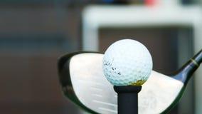 Fermez-vous vers le haut de la boule sur le golfeur retiré par pièce en t prenant l'oscillation frappant la boule de golf outre d Photos libres de droits