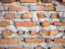 Fermez-vous vers le haut de la brique orange sur le mur en béton pour le fond images stock
