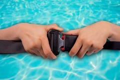 Fermez-vous vers le haut de la ceinture de sécurité d'utilisation de deux mains Photographie stock