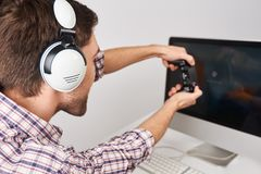Fermez-vous vers le haut de la coordonnée du jeune gamer masculin barbu jouant des jeux sur le PC avec le contrôleur dans des éco Images libres de droits