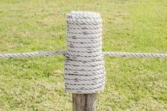 Fermez-vous vers le haut de la corde fatiguée dans le poteau en bois avec le backgrou d'herbe verte photos stock
