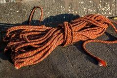 Fermez-vous vers le haut de la corde tressée rouge sur l'asphalte Photo libre de droits