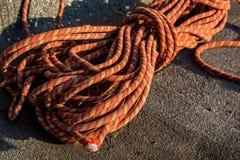 Fermez-vous vers le haut de la corde tressée rouge sur l'asphalte Image stock