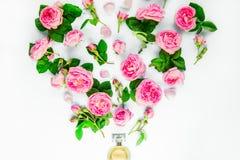 Fermez-vous vers le haut de la disposition créative avec la bouteille de parfum et pilotez les fleurs roses de thé rose sur le fo photos stock