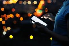 Fermez-vous vers le haut de la femme à l'aide du comprimé numérique pendant la nuit photo libre de droits
