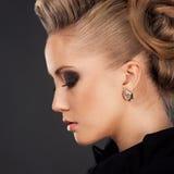 Fermez-vous vers le haut de la femme blonde avec la coiffure de mode Photo stock