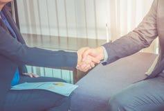 Fermez-vous vers le haut de la femme d'affaires et de l'homme d'affaires serrant la main pour le congratu Image stock