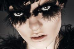 Fermez-vous vers le haut de la femme de portrait avec les plumes noires sur des yeux Image libre de droits