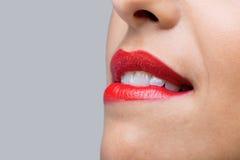 Fermez-vous vers le haut de la femme mordant ses languettes rouges photographie stock libre de droits