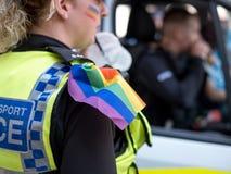 Fermez-vous vers le haut de la femme de police avec des couleurs d'arc-en-ciel peintes sur son visage, et porter un drapeau d'arc Photographie stock libre de droits