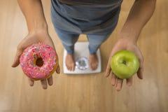 Fermez-vous vers le haut de la femme sur l'échelle de poids se tenant en son fruit et beignet de pomme de main comme choix de sai Photo libre de droits