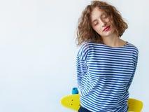 Fermez-vous vers le haut de la fille de sourire réfléchie de brune avec les cheveux bouclés Image stock