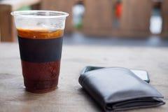 Fermez-vous vers le haut de la glace de l'americano ou du café noir avec le portefeuille Images libres de droits