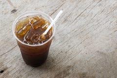 Fermez-vous vers le haut de la glace de l'americano ou du café noir sur le fond en bois Image libre de droits